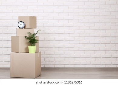 Cardboard boxes with household stuff on brick wall background