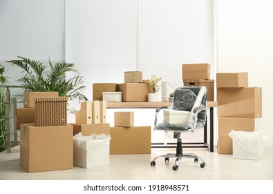 Cardboard boxes and packed chair in office. Moving day
