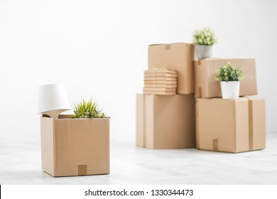 Cardboard boxes with things are stacked on the floor against the background of a white wall close up. Books and table lamps and green plants in pots. The concept of moving to a new home. Copy space.