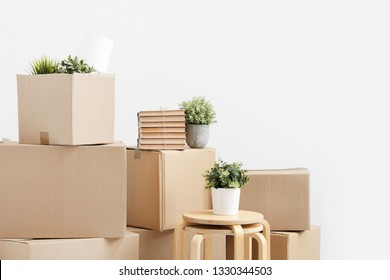 Cardboard boxes of things are stacked on the floor against a white wall. Books and table lamps and green plants in pots. The concept of moving to a new home. Copy space.