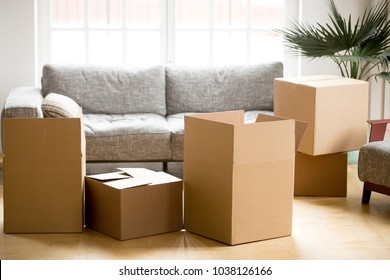 Cardboard carton boxes with personal belongings household stuff in modern living room, many packed containers on moving day in new home, relocation or house removals delivery service concept
