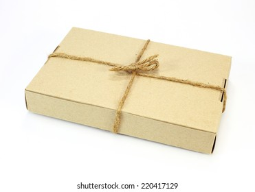 Cardboard carton wrapped with brown paper and tied with cord on white background