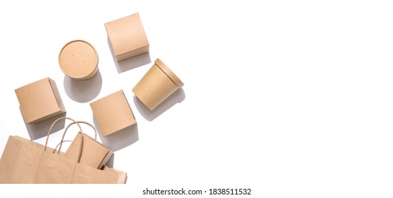 Cardboard containers for food, drinks and items drop out of the craft bag.  Isolated on white background, top view. Copy space. Delivery, takeaway food, eco-friendly packaging concept. Nobody. - Shutterstock ID 1838511532