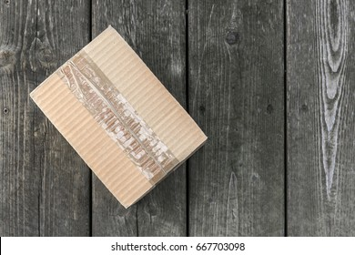 Cardboard delivery parcel box delivered to doorstep on old wood background