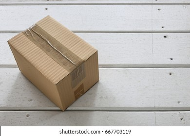 Cardboard delivery parcel box delivered to doorstep closeup