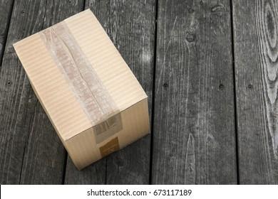 Cardboard delivery parcel box delivered to doorstep on old wood background