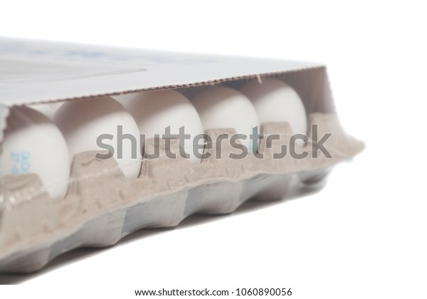 Cardboard egg box with chicken white eggs isolated on white background
