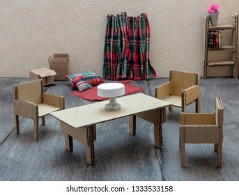 Cardboard furniture, circular economy. Cardboard chairs, table and cupboard in a living room on doll house format.