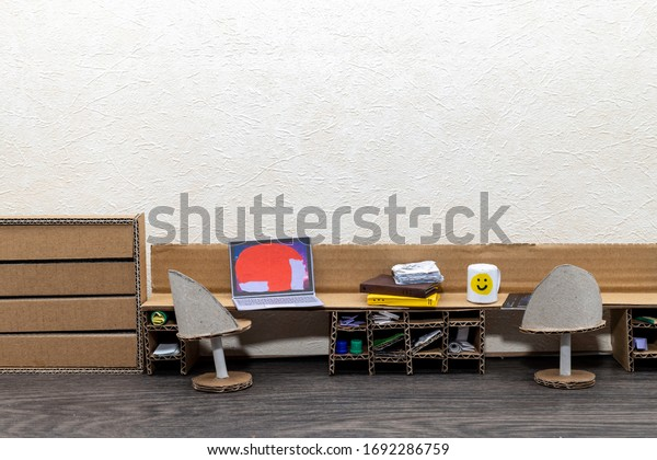 Cardboard furniture in a doll house. Home office with a cardboard desk and dresser. Chairs from paper rolls. Room for copy.