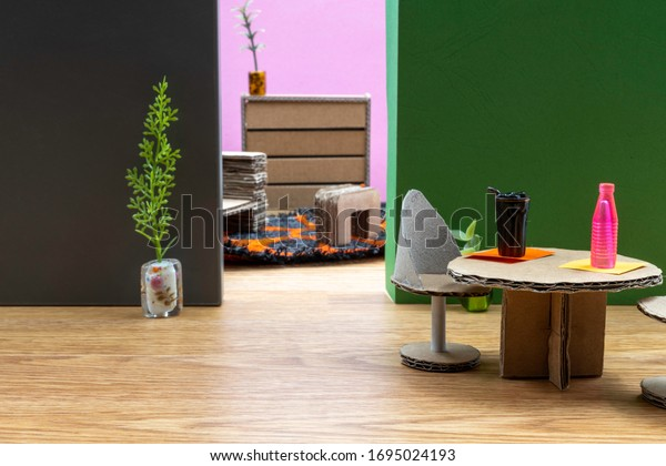 Cardboard furniture in a doll house. Cardboard table and chairs on a wooden floor. Room for copy.