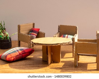 Cardboard furniture out of recycled cardboard. Chairs, table, red checkered cushions and fake plant. Dollhouse furniture. Sunshine in the room. Room for copy.