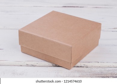 Cardboard gift box on wooden background. Brown present box on white wooden table. Carton package for gifts.