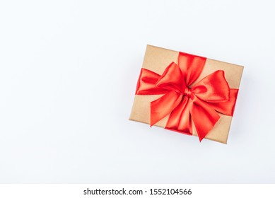 Cardboard gift box with red bow on white background. Flat lay. Top view. Copy space for your text.