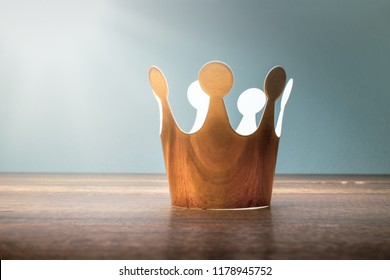 cardboard golden crown on wood table with morining light.
