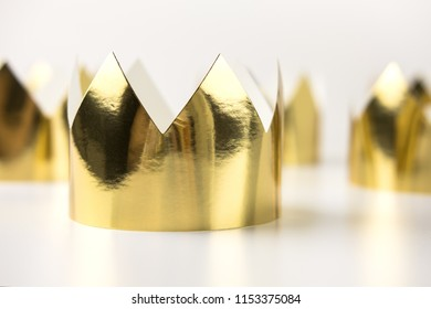 Cardboard golden crowns lying on a white table. Minimalistic style.
