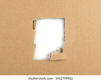 Cardboard hole background. Carton torn with copy space, kraft paper frame top view