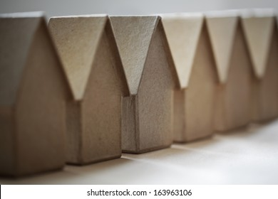 Cardboard houses in a row concept for community, neighborhood or real estate market