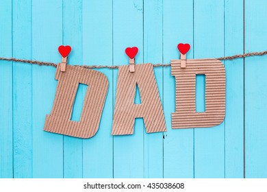 Cardboard letters DAD hanging on clothespins on a blue wooden background. Happy fathers day concept.