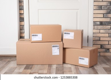 Cardboard parcel boxes on floor near apartment entrance. Mockup for design