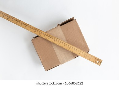 Cardboard shipping box placed on white background. Leaning on it is a wooden yardstick whit centimeters and inches fractions scales. Association of measuring a box for delivery.