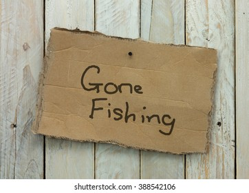 Cardboard sign on a wooden background saying gone fishing