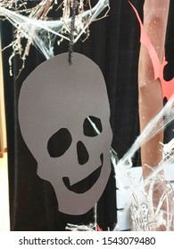 A cardboard skull with holes in the eyes, nose and mouth hangs on a decorative thread against a black cloth and white threads in the shape of a web. Halloween concept.