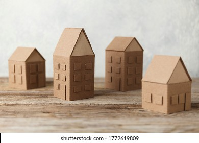 Cardboard toy houses on wooden background. Sale or rental of housing. Neighbors in house. Comfortable life in suburbs.