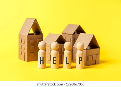 Cardboard toy houses on yellow background with help sign. Falling property prices. Economic depression.