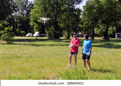 CARDET, FRANCE - MAY 25: Two adults in the countryside having fun with a drone equipped with a mini camera, may 25, 2015.