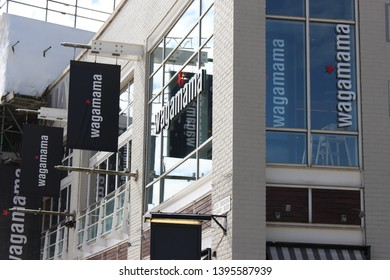 Cardiff Bay, Cardiff UK - May 10 2019:  A photograph of the exterior of the Wagamama restaurant in Cardiff Bay, with scaffolding from construction work behind.