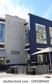 Cardiff Bay, Cardiff, United Kingdom - 10 May 2019: An exterior photograph of eateries in Cardiff Bay including Cote Brasserie and Wagamama in the sunlight.  Large 'Eat, Drink, Relax' mural on wall.