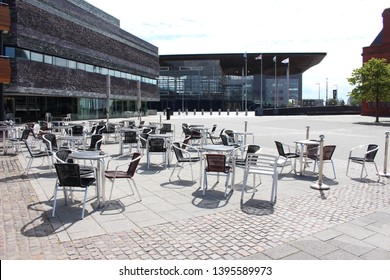 Cardiff Bay, Cardiff, United Kingdom - 10 May 2019: Empty chairs for the Wales Millennium Centre cafe in the sunlight. The National Assembly for Wales's Senedd building in the background.