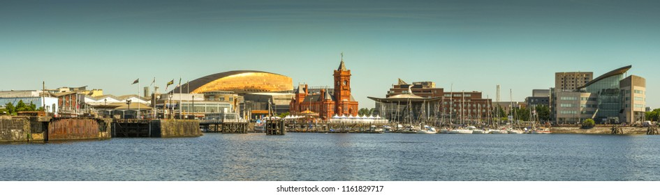 CARDIFF BAY, CARDIFF, WALES - JULY 2018: Panoramic view of the Cardiff Bay waterfront. In the centre is the roof of the Wales Millennium Centre and the orange brick of the historic Pierhead Building.