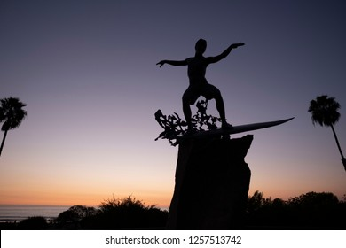 "Cardiff by the Sea, California / USA 12/11/2018. The ""Cardiff Kook"" statue stands guard over Cardiff state beach at sunset in San Diego California. Cardiff is a world class surfing destination."