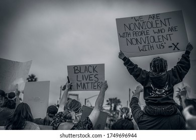 Cardiff by the Sea, California / USA - June 4th 2020: This is a close up photo of people holding signs for a protest against police brutality.