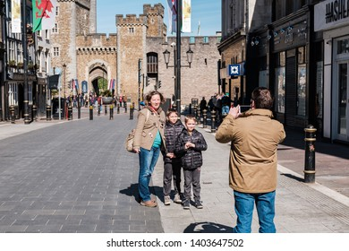 Cardiff, UK. April 2018. A family posing for a picture with Cardiff Castle in the background. Dad is taking the picture of mum and two children.