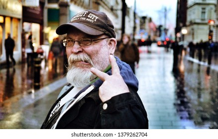 Cardiff, UK / April 24th 2019 : unfriendly hostile man with ungroomed grey beard in city centre on rainy day with shop lights reflected on pavement.