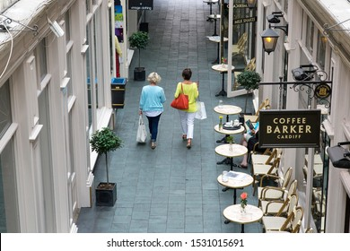 Cardiff, UK: August 05, 2016: Two fashionable women walk through an arcade with retail shops and a street cafe on either side. The women are both middle aged and very well dressed.