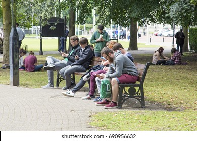 Cardiff, UK: August 2016: Young adults sitting on a park bench playing Pokemon Go. Pokémon Go is a free-to-play location based augmented reality mobile game developed by Niantic.