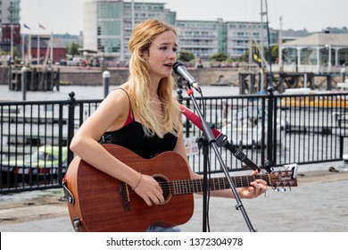 Cardiff, UK. August 2017. A young blonde lady with freckles busking on her Tanglewood guitar, Cardiff Bay. Mermaid Quay in the background.