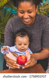 Cardiff, UK. Circa 19th May 2019. Close up portrait of adorable mixed race baby boy with his mother, playing with an apple.