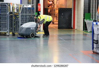Cardiff uk January 25 2019 workplace cleaner in warehouse cleaning floor with machine wearing high visibility clothing