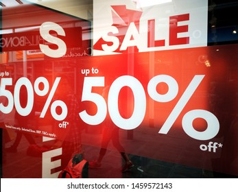 Cardiff, UK: July 20, 2019: Shop front display window with a large sales poster advertising a sale with up to 50% discounts.
