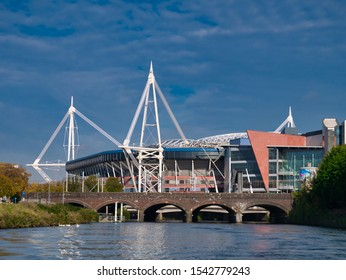 Cardiff, UK - Oct 22, 2019: The Millennium Stadium / Principality Stadium in Cardiff, Wales, UK - taken from the River Taff, with the rail bridge next to Cardiff Central Station in the foreground.