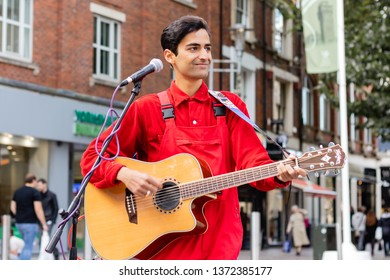 Cardiff, UK. October 2017. Young Asian man busking on his guitar in The Hayes, Cardiff. He is wearing a bright red shirt and dungarees; and has an owl earring.