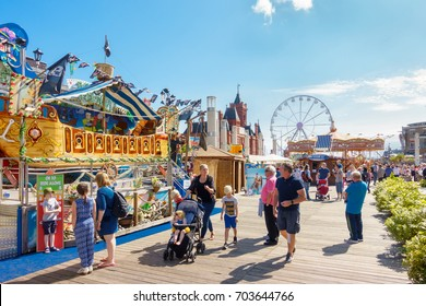 Cardiff, United Kingdom -  August 26, 2017: People enjoying themselves on a sunny day at the Cardiff Bay Beach Fair, an urban seaside beach fair at Roald Dahl Plass in Cardiff Bay, Cardiff.