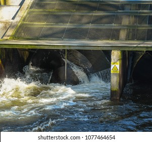 CARDIFF, WALES - APRIL 2018: Close up of water flowing out of an Archimedes Screw Turbine at the hydro electric plant on the River Taff at Radyr