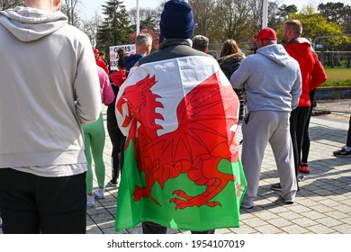 Cardiff, Wales - April 2021: Person wrapped in a Welsh flag in a crowd of people in Cardiff city centre