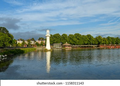 CARDIFF, WALES - AUGUST 2018: Wide angle view of Roath Park Lake in Cardiff. The lighthouse is the The Scott Memorial in memory of Captain Scott who left Cardiff on his polar expedition.