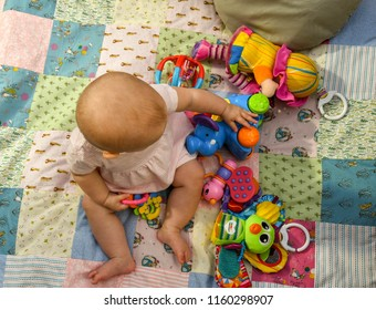 CARDIFF, WALES - JULY 2018:  Baby girl sitting on a fabric quilt playing with colorful plastic toys, with other toys around.